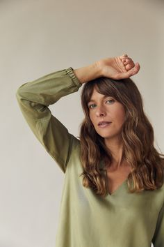 This is a green relaxed fitting blouse with long sleeves, a v-shaped neckline and an elastic band around the wrists. It is made of a very soft, luxurious fabric. We recommend tucking it in! 100% TENCEL™ fibers from Austria, woven in Spain and sustainably dyed using the Iris method. Made in Germany. Green Blouse, V Neck Blouse, Organic Cotton, Neckline, Long Sleeve, Fabric, Austria, Iris, Spain