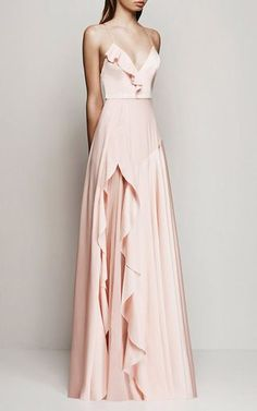 This sleeveless **Alex Perry** gown is rendered in satin crepe and features a deep v-neck with thin camisole-style shoulder straps that connect at the back, a fitted bodice with a ruffle detail at the front, and a floor length bias draped skirt with a ruffle trimmed split at the side that exposes a tonal underlay.