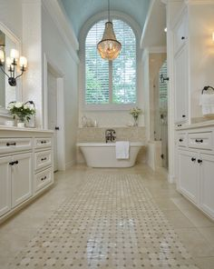 Bathroom - Beautiful mosaic tile carpet with a back splash wrapped around the graceful tub. More than adequate storage with wall sconces & a graceful chandelier hung in front of an arched window. Total elegance!