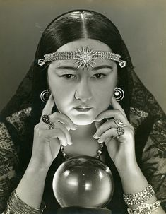 Female fortune teller with a crystal ball. photograph by Froelich, Russell, 1930s.