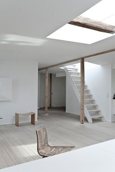 Simple interior, raw timber structure, light wood floor, simple wooden bench/stool and rattan chair