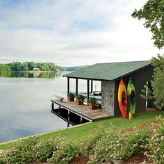 "I want to find an old kayak I can repaint to display like this on the boathouse. Cute and ""lakey"" looking.  (We like to kayak.)  I also love the plants on the dock."