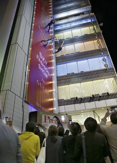 """Sky fashion show (May 7,2014,Ginza,Tokyo) People look up at models walking on a runway set vertically on the wall of the 42-meter-tall Sony Building in Ginza as they display creations by Gucci during an event titled the """"Sky Fashion Show"""" on Wednesday nig"""