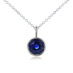 Solitaire bezel blue sapphire in 14-karat white gold with a detachable 16 inch cable chain. The stone is 6.5mm wide. The sapphire displays a deep blue hue.