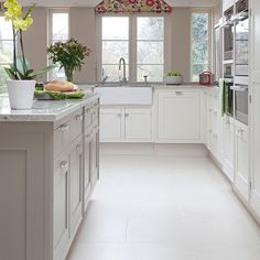 Pale grey and white kitchen. Pale grey is a timeless colour choice for the kitchen. White cabinets with granite worktops and sleek built-in appliances keep the look fresh. Similar kitchen units, Smallbone of Devizes, Similar appliances, Miele.