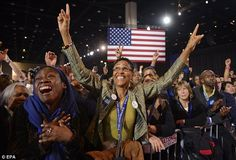 Nearing the finish line: Obama supporters at his election party in Chicago raise their arms as predictions put the President in the lead over Republican candidate Mitt Romne