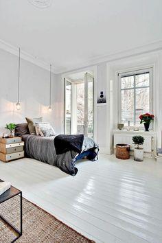 parquet blanc, intérieur tout blanc avec grand lit et tapis moquette
