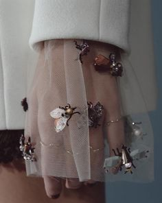 Dior - tulle sleeves with enamel bugs