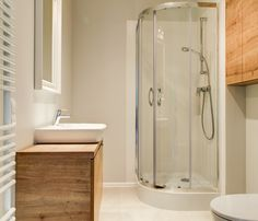 Aranżacja łazienki w minimalistycznym stylu. Białe wnętrze zostało ocieplone drewnianymi elementami. Przeszklone drzwi kabiny prysznicowej dodatkowo powiększają przestrzeń. Bathtub, Bathroom, Space, Standing Bath, Washroom, Floor Space, Bathtubs, Bath Tube, Full Bath