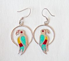Bright Mexican silver parrot earrings. Sterling with inlaid turquoise and enamel comprise this colorful pair sitting on their perches. Great for the summer, beach, and your tropical getaways!  SIZE: From tops of wires: 1-3/4 x 3/4-- 4.5cm x 2cm HALLMARKS: Mexico; 925 CONDITION: Good used condition. One wire slightly bent. No cracks to turquoise or enamel.  Wherever possible, we use recycled packing materials in our shipping. This enables us to help the environment, and continue to offer…
