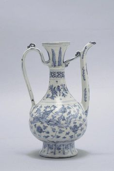 A porcelain ewer China, Ming Dynasty, 16th century. An important ewer modeled according to the Islamic style; it presents a slender shape characterized by an elegant handle and the long spout. The surface of the body is decorated with phoenixes flying between lotus flower branches. The base bears the four-character mark of Xuande in underglaze blue. A ewer of rare typology exported for the Islamic market. h 24 cm