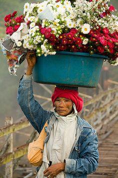 Mon woman with basket of flowers on her head in Sangklaburi Thai