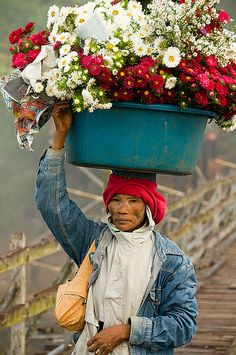 Mon woman with basket of flowers on her head in Sangklaburi Thai