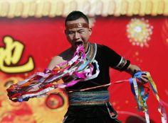 Homem puxa fitas de dentro de sua boca em demonstração de força durante as celebrações do Ano Novo Chinês, em Pequim. Foto: Kim Kyung-Hoon/Reuters