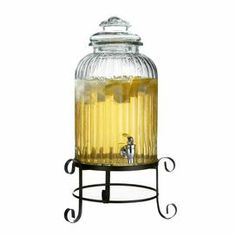 "Glass beverage dispenser with ribbed details. Features a scrolling metal stand.    Product: Beverage dispenser and standConstruction Material: Metal and glassColor: Clear and blackFeatures: 3 Gallon capacityDimensions: 21"" H x 12.5"" Diameter (overall)"
