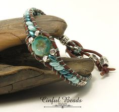 A single wrap bracelet in beachy seafoam tones. Superduo beads have been stitched onto 1.5mm natural brown leather cord. It features a Czech glass Hawaiian flower bead as a center focal. Tibetan style silver plated beads are interspersed for further adornment. The clasp is an adorable TierraCast button with a decorative design. Its a great everyday bracelet that will look great with jeans and a t-shirt.  When the bracelet is closed its 7 around. The sides are 3/8 wide and its 5/8 wide at the…