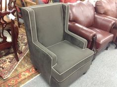 Grey Upholstered Easy Chair - Dark grey upholstery with a light grey piping.  Modern wing chair style   - http://takeitorleaveit.co/2013/10/19/grey-upholstered-easy-chair/