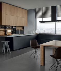 Twelve kitchen with base units in black frosted glass and anodized aluminium, worktop with double thickness 12 and 52 mm in DuPont Corian pearl gray. Tall units and wall units in elm. Modular equipments Shaker in black embossed lacquered aluminium with backs in elm. Island hood Flat in black mat lacquer and transparent glass. Dolmen due table in solid oak. Harmony chairs with structure in black mat lacquered metal and body in spessart oak.