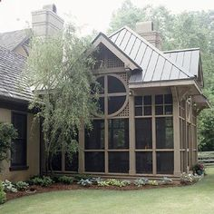 A screened porch allows you to enjoy the outdoors without mosquitoes. I love the details on this Tudor-style porch.
