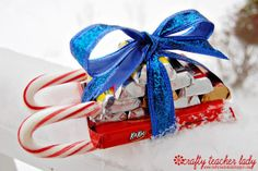 Crafty Teacher Lady: Candy Cane Sleigh Tutorial - 2 candy canes, 1 full sized KitKat bar, 10 snack sized chocolate bars and ribbon.