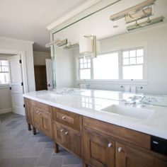 Grey herringbone floors, white marble counters, full mirror with built in fixtures. (Minus the middle one) Can be done with white cabinets.