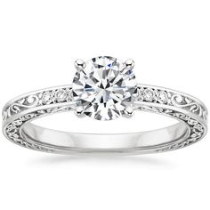 This exquisite antique-style setting is adorned with an engraved scroll pattern on the top and sides, with the top of the ring accented by six dazzling diamonds.