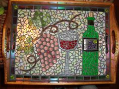 This is a beautiful mosaic tray that I designed myself. It has incorporated a wine bottle, wine glass, grape leaves and a wine bottle with a cork. It