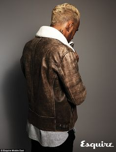 Hamilton with his back to the camera shows off his brown leather jacket with a sheepskin lining at the top