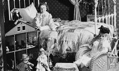 Girl seated in bed with roomful of toys, including an antique dollhouse. c.1902 [Library of Congress]
