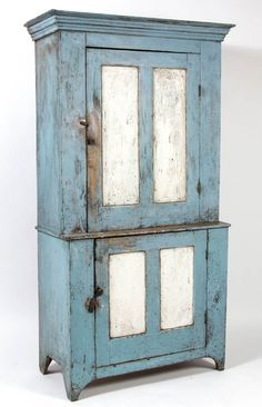 SOUTHERN, PROBABLY VIRGINIA, PAINTED POPLAR STEP-BACK WALL CUPBOARD, one piece, the complex, applied three-part cornice above a single hinged double-panel door concealing two fixed shelves over a single hinged double-panel door concealing single fixed shelf, cut-out skirt and solid ends. Retains an old blue-and white-painted surface.