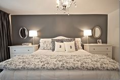 Master bedroom with dressers as nightstands, grey curtains, grey accent wall