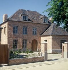 Kleiner 'huisje' tegen groter huis aan - mooie steen en houten deur