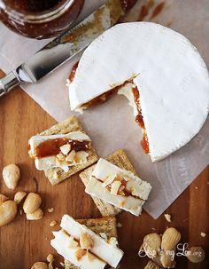 Recette pour l'apéritif : un fromage de brie est garni de confiture de figues et d'amandes hachées puis coupé en lamelles servies sur des tranches de pain.