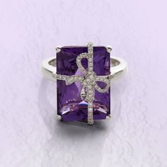 Amethyst and Diamond Ring. Set with a rectangular step-cut Amethyst, accented with a ribbon set with brilliant-cut Diamonds, British hallmark. Signed David Jerome, stamped G18K, gold (750) for 18 carat Gold, British hallmark for Birmingham, sponsor's mark W1b. Amethyst mid purple, transparent, stone appears clean, very minor abrasions to facet edges, measuring approximately 17.6 x 12.5 x 9.6mm, calculated to weigh approximately 14.00 carats. Diamonds bright and lively... || Sotheby's