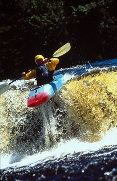 Action shot of a man kayaking through some white water in Maine. Have you ever experienced this rush?