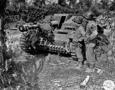 American tankers from the 3rd Armored Division look at a dead German tanker blown from the hatch of his Stug III assault gun after which he came to rest on the barrel.