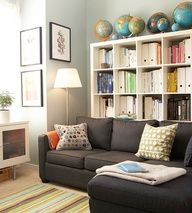 """Neutral Base  A small living room lives large in a peaceful palette of blue-gray walls, small-scale charcoal sectional, and warm orange accents. White bookcases line the wall, where a collection of globes and bookbindings sorted by color add more accent hues. Underfoot, a multicolor-stripe rug balances the solidly neutral upholstered furniture."""" data-componentType=""""MODAL_PIN"""