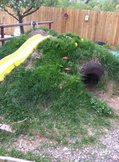 """A 'bear cave' hill with slide - from My Intentional Play ("""",) // ran across a piece of advice for building hill:  pile up dirt until right shape and height (landscape mesh will not help); grass will not grow in heavy traffic areas (although this one seems to have some nice grass) - kp"""