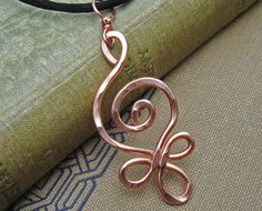 We swirled and hammered 14 gauge copper wire to hand make this Celtic influenced spiral design. The pendant measures about 1 1/2 - 1 7/8 (3.9 -