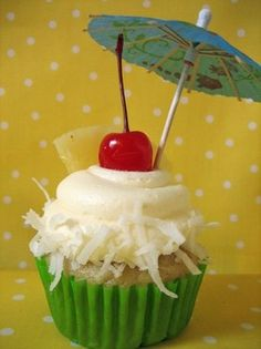 This cupcake was decorated using a cherry, pineapple and a cute drink umbrella.