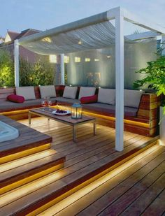 A pergola designed with a canopy and deck. Has under-rail lights for benches/steps.