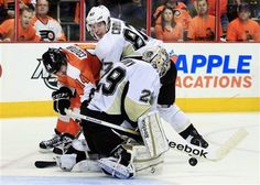 Philadelphia Flyers' Sean Couturier (14) is pushed away from Pittsburgh Penguins goalie Marc-Andre Fleury by Sidney Crosby