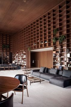 Floor-to-ceiling grids of wooden shelves cover double-height walls inside this apartment in São Paulo by local office Studio MK27