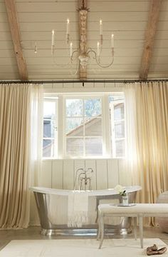 love this bathroom! - silver freestanding tub under a gorgeous chandelier hanging from a peaked ceiling with beams...and those amazing curtains!