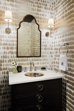 The powder room is positively luxe with a hammered silver sink basin, silver Queen of Spain wallpaper, and glossy floor tile. Sign. Us. Up.