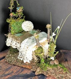 Moss covered Fairy bed is 14 inches long, 12 inches at the tallest point and about 6 inches wide. It is constructed out of twigs, small sticks, moss, acorns and small pine-cones. This bed is resting on a small sliver of baked bark. Bed linens are constructed from crocheted doilies, lace, scrap fabric and burlap. This little bed is packed with detail and whimsical charm. It is hand crafted, one of kind and made with lots of love