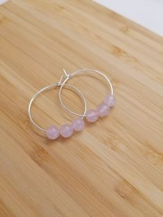 These beautiful handmade sterling silver hoops feature beautiful Rose Quartz beads. They are a stunning way to wear gorgeous gemstones. Rose Quartz is the stone of universal love, encouraging unconditional love. Promotes love, self-love and friendship.  #handmadejewellery #sterlingsilverjewelelry #gemstonejewellery Sterling Silver Hoops, Handmade Sterling Silver, Beautiful Roses, Rose Quartz, Gemstone Jewelry, Friendship, Handmade Jewelry, Jewelry Making, Jewellery