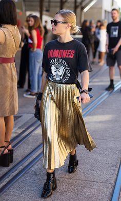Muito amor em um look só: camiseta de banda de rock, saia plissada dourada e botas.