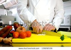 Vegetables on cutting board and chef hands detail, restaurant kitchen on background by MilaCroft, via ShutterStock