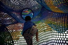 Child crawling through crochet playground - children's park-in-a-park